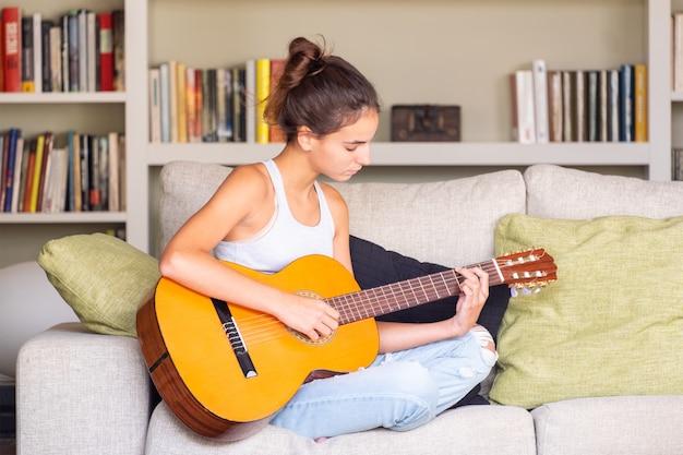 Молодая девушка играет на гитаре, сидя на диване у себя дома