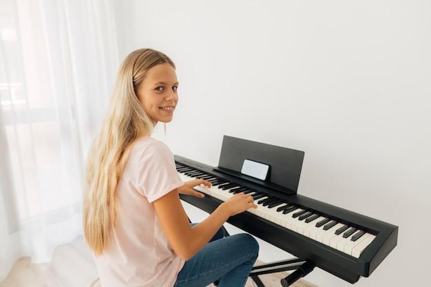 집에서 키보드 악기를 연주하는 어린 소녀