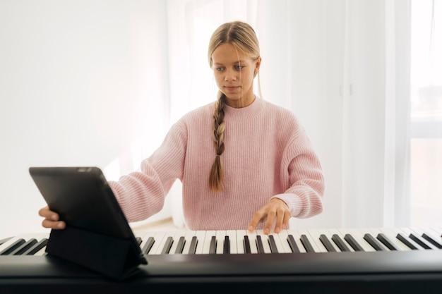 Молодая девушка играет на клавишном инструменте дома