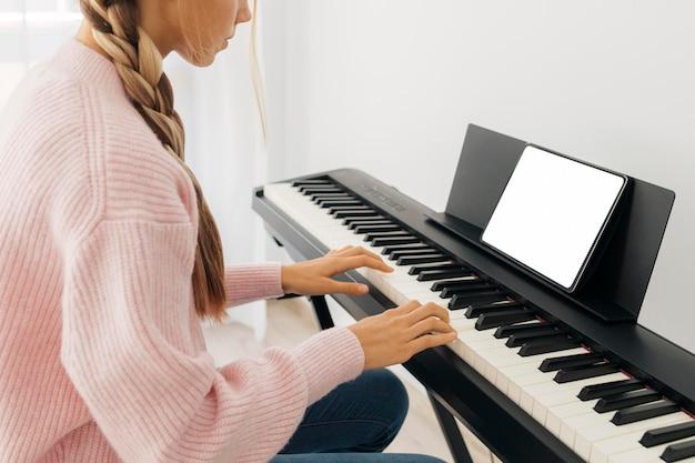 Молодая девушка играет на клавишном инструменте