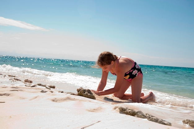 Young girl playing in the sand on belizean isle in belize
