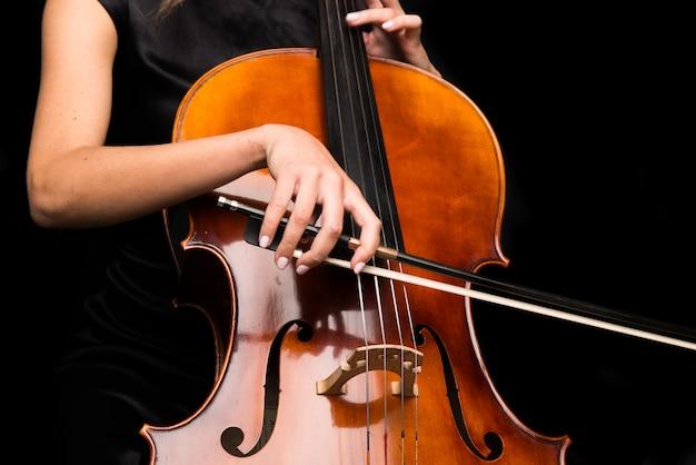 孤立した黒い背景にチェロを弾く少女
