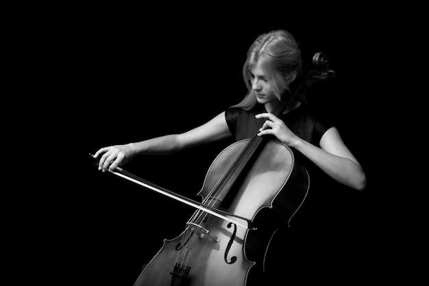 Молодая девушка играет на виолончели на черном фоне