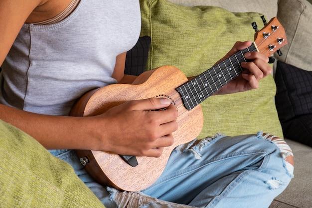 Молодая девушка играет укулеле, сидя на диване у себя дома