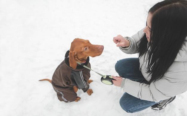 Молодая девушка играет с собакой в снежный зимний день
