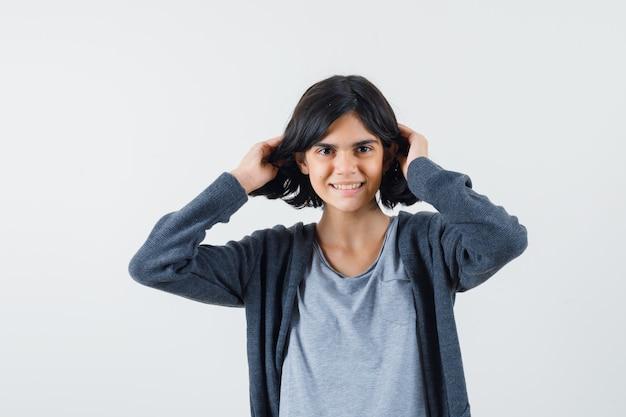 Молодая девушка играет с волосами в светло-серой футболке и темно-серой толстовке с капюшоном на молнии и выглядит мило.