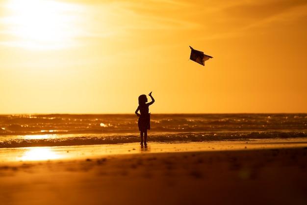 Молодая девушка играет с воздушным змеем на пляже на закате