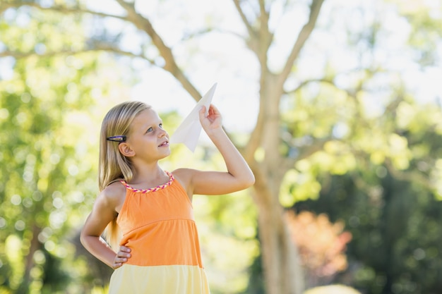 Young girl playing with a paper plane