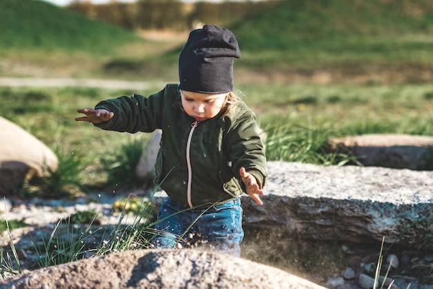 岩の上の砂で遊ぶ少女