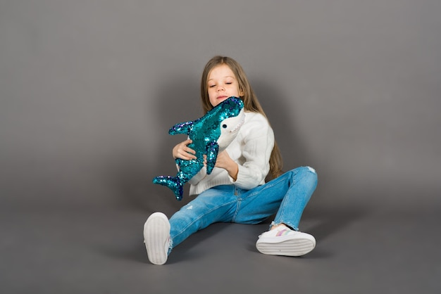 Young girl playing with shark toy in a yellow