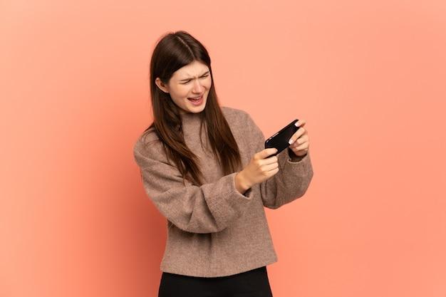 Молодая девушка играет с мобильным телефоном