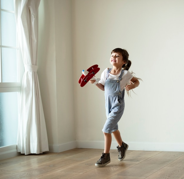 Young girl playing with a toy plane
