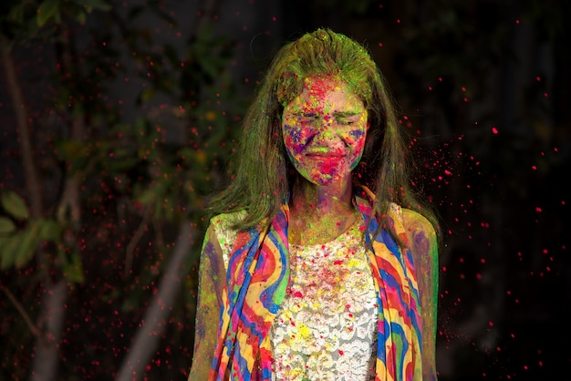 A young girl plays with colors. the concept for indian festival holi. color splash.