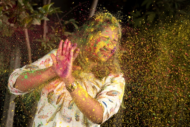 Young girl plays with colors on the occasion of holi. concept for indian festival holi. color splash.