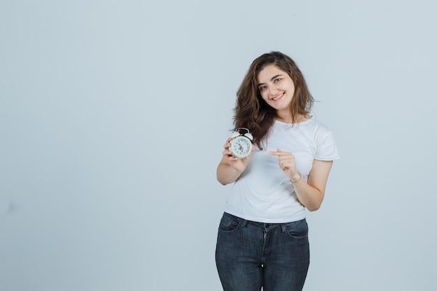 Молодая девушка указывая будильник в футболке, джинсах и радостный взгляд. передний план.