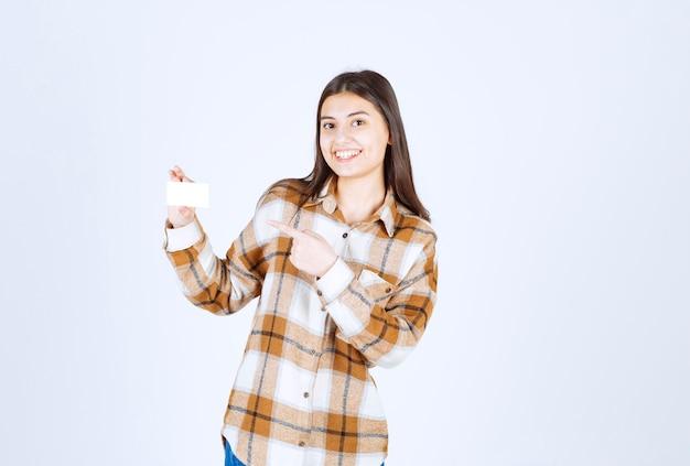 Молодая девушка, указывая на чашку чая на белой стене.