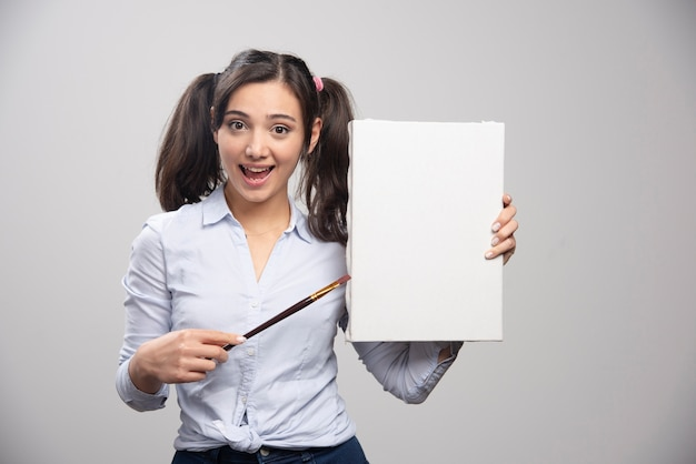 絵筆で空のキャンバスを指している若い女の子。