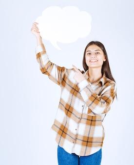 白い壁に空のテキストの雲を指して若い女の子。