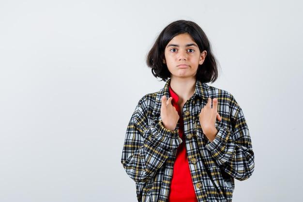 체크 셔츠와 빨간 티셔츠를 입은 검지 손가락으로 자신을 가리키고 진지한 정면을 바라보는 어린 소녀.