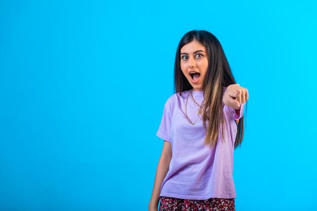 Молодая девушка указывая на что-то с жестом пальца.