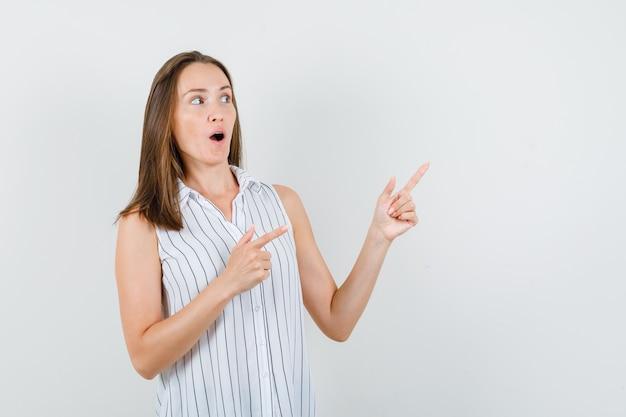 Молодая девушка указывая прочь в футболке и глядя любопытно, вид спереди.