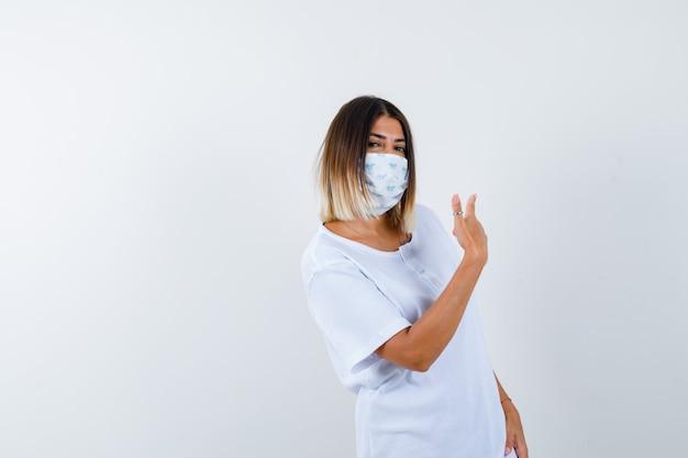 흰색 t- 셔츠와 마스크에 검지 손가락으로 뒤에 가리키는 자신감을 찾고 어린 소녀. 전면보기.