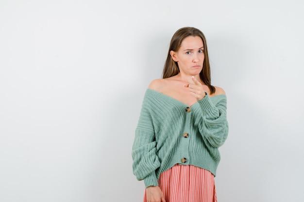 Giovane ragazza che punta alla telecamera con il dito indice in maglieria, gonna e che sembra seria. vista frontale.