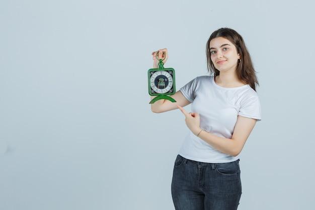 Giovane ragazza che indica orologio in t-shirt, jeans e che sembra felice, vista frontale.