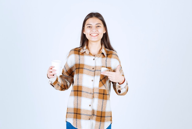 Young girl pointing at cup of tea on white wall.