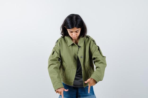 Giovane ragazza che punta verso il basso in maglione grigio, giacca kaki, pantaloni jeans e sembra concentrata. vista frontale.