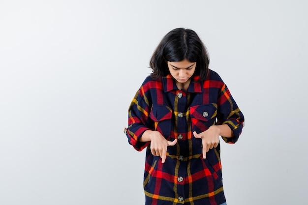 Giovane ragazza che punta verso il basso con l'indice in camicia a quadri e sembra seria. vista frontale.