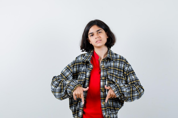 Young girl pointing down with index fingers in checked shirt and red t-shirt and looking happy. front view.