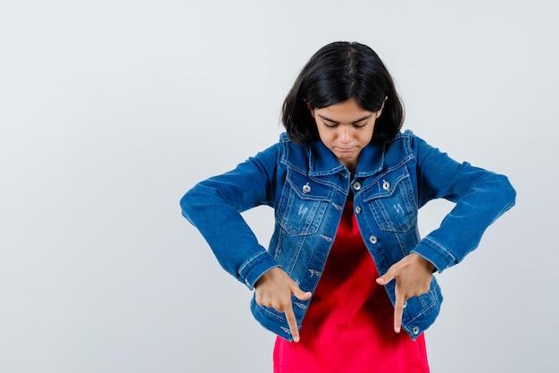 Giovane ragazza che punta verso il basso con l'indice in maglietta rossa e giacca di jeans e sembra carina. vista frontale.