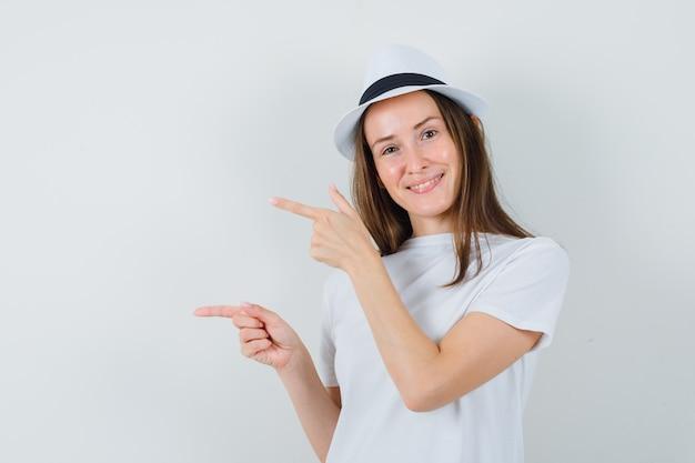 白いtシャツ、帽子、陽気に見える左側に指を指している若い女の子。正面図。