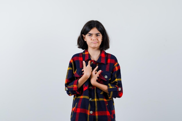 Young girl pointing at herself in checked shirt and looking cute , front view.