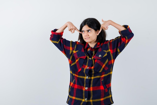 Young girl pointing herself in checked shirt and looking serious. front view.