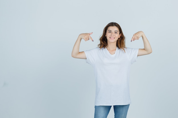 어린 소녀 t- 셔츠, 청바지에 자신을 가리키는 자랑 스 러 워 찾고. 전면보기.