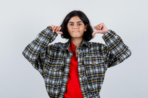Ragazza che indica se stessa con l'indice in camicia a quadri e maglietta rossa e sembra felice. vista frontale.