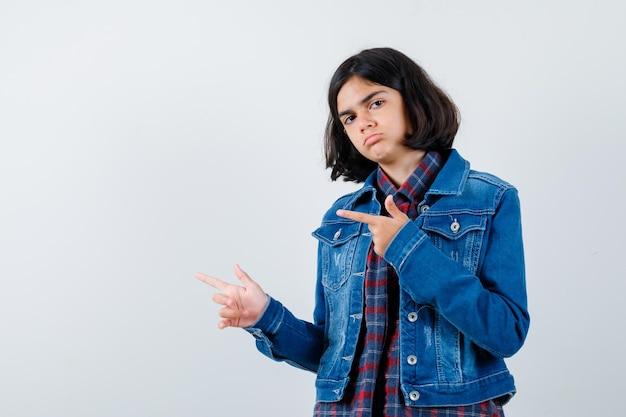 체크 셔츠와 진 재킷을 입고 왼쪽을 가리키며 진지한 표정을 짓고 있는 어린 소녀