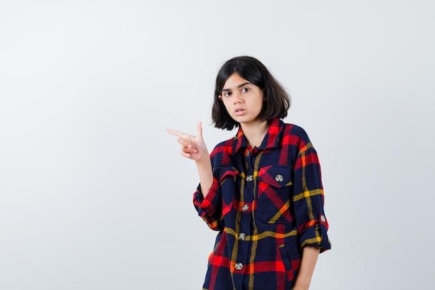 체크 셔츠에 왼쪽을 가리키는 어린 소녀와 심각한 찾고 전면 보기.