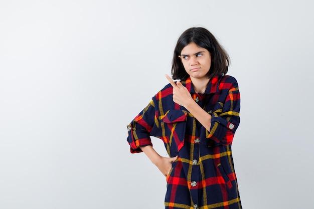 チェックシャツで腰に手を握り、かわいく見える、正面図で左側を指している若い女の子。