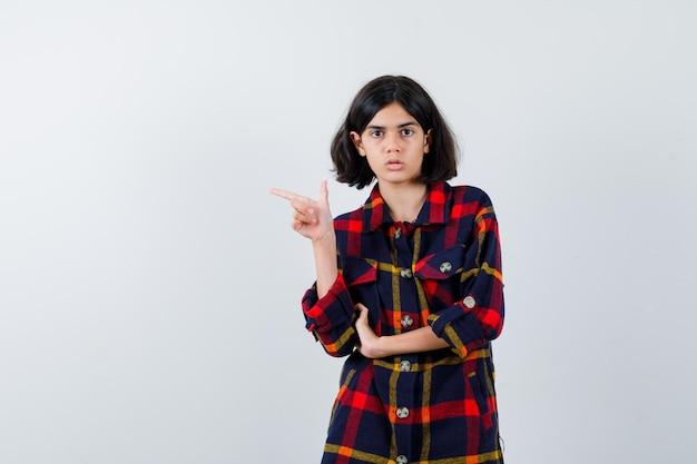 Молодая девушка указывая влево, держа руку на предплечье в клетчатой рубашке и серьезная, вид спереди.
