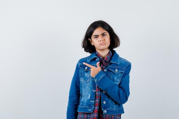 Молодая девушка указывает влево указательным пальцем в клетчатой рубашке и джинсовой куртке и серьезно выглядит, вид спереди.