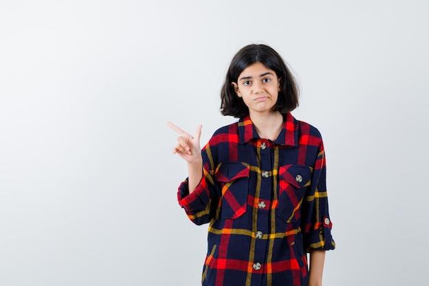 Молодая девушка указывая влево указательным пальцем в клетчатой рубашке и выглядит мило, вид спереди.