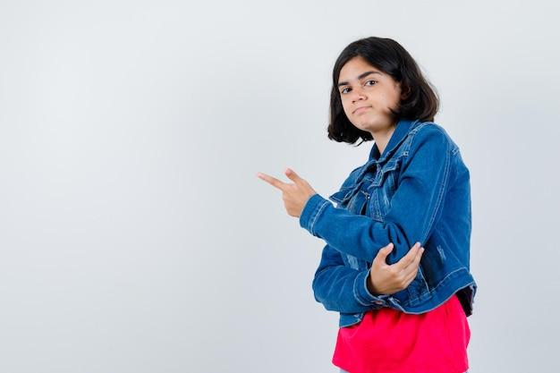 Молодая девушка указывает влево указательным пальцем в красной футболке и джинсовой куртке и выглядит серьезной. передний план.