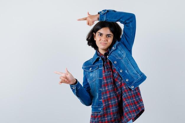 チェックシャツとジージャンの人差し指で左を指して、かわいい、正面図を探している若い女の子。