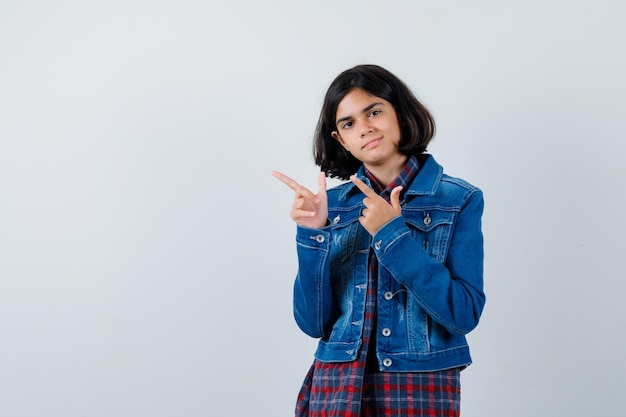 Молодая девушка указывает влево указательными пальцами в клетчатой рубашке и джинсовой куртке и выглядит мило, вид спереди.
