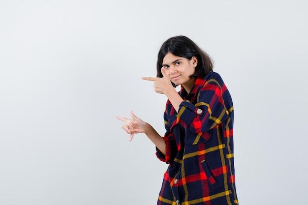 Молодая девушка указывая влево указательными пальцами в клетчатой рубашке и выглядит счастливой. передний план.