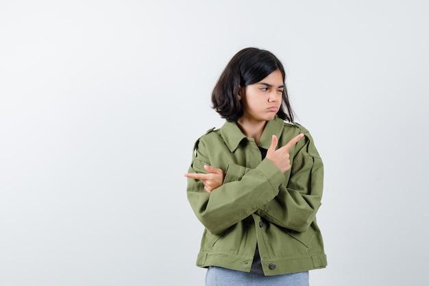 Giovane ragazza che punta in direzioni opposte in maglione grigio, giacca color kaki, pantaloni jeans e sguardo concentrato, vista frontale.
