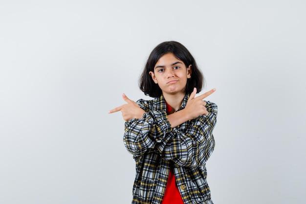 チェックのシャツと赤いtシャツで反対方向を指し、真剣に見える少女。正面図。